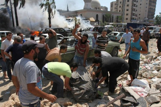 People react as they remove a dead body from the scene of an explosion outside one of two mosques in Lebanon's northern city of Tripoli,
