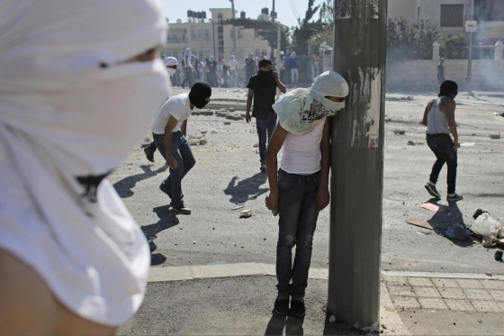 A Palestinian stone-thrower takes cover behind a street pole during clashes with Israeli police in Shuafat