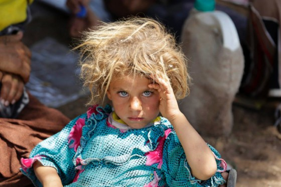 A girl from the minority Yazidi sect, fleeing the violence in the Iraqi town of Sinjar, rests at the Iraqi-Syrian border crossing in Fishkhabour
