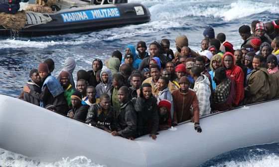 Migrants sit in a boat off the coast of Sicily during a mission by the Italian navy as part of its M