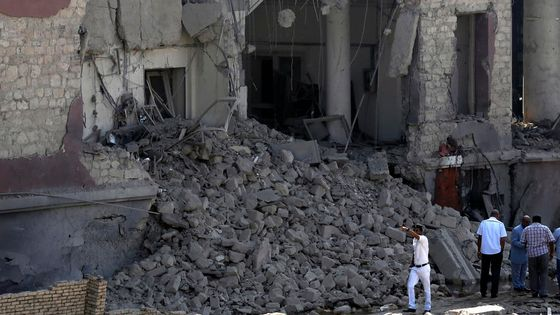 Egyptian policemen stand at the base of the crumbled facade of the Italian consulate following a blast that killed at least one person in Cairo, Egypt, Saturday, July 11, 2015. An Italian embassy official said the consulate was closed at the time of the explosion and no staff members were injured. (AP Photo/Hassan Ammar)