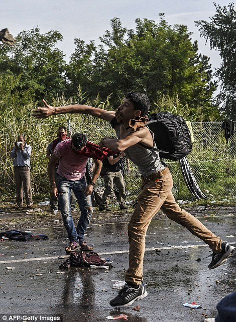 2C62594800000578-3236418-A_refugee_throws_a_stone_towards_Hungarian_riot_police_after_the-m-26_1442424117788