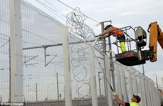 2E1550FE00000578-0-Workers_reinforce_a_fence_with_razor_wire_to_protect_the_Eurotun-a-111_1446736637433