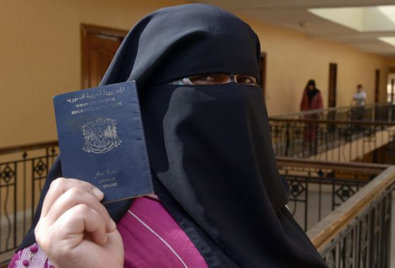 Fatima, a 45-year-old Syrian refugee from the central city of Homs, flashes her passport in Tangier, Morocco, on October 28, 2013. Fatima arrived in Morocco two months ago with her husband and their seven children and lives now with a dozen of other Syrian families on the sixth floor of a building on Tangier's seafront. AFP PHOTO /FADEL SENNA (Photo credit should read FADEL SENNA/AFP/Getty Images)
