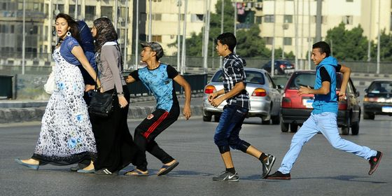 In this Monday, Aug. 20, 2012 photo, an Egyptian youth, trailed by his friends, grabs a woman crossing the street with her friends in Cairo, Egypt. Several youth groups and activists have held protests and sit ins against sexual harassment, particularly during Muslims holidays which witness a surge of mobs of teenagers sexually harassing women in groups, in the streets. (AP Photo/Ahmed Abdelatif, El Shorouk Newspaper)