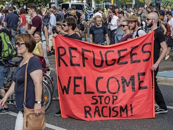 Germany-Headline-News-Now-Protesters-demonstrate-with-a-banner-saying-Refugees-welcome