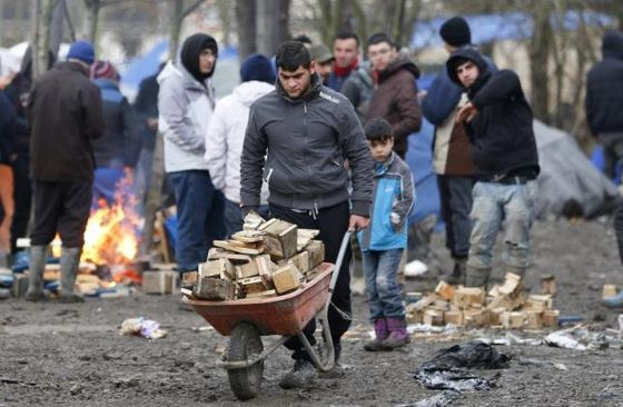 A migrant pushes a wheelbarrow in a muddy field at a camp of makeshift shelters for migrants and asylum-seekers from Iraq, Kurdistan, Iran and Syria, called the Grande Synthe jungle, near Calais, France, February 3, 2016.  REUTERS/Yves Herman