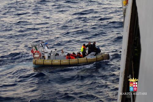 migranter-i-gummibåt-ved-italiensk-kystvaktskip