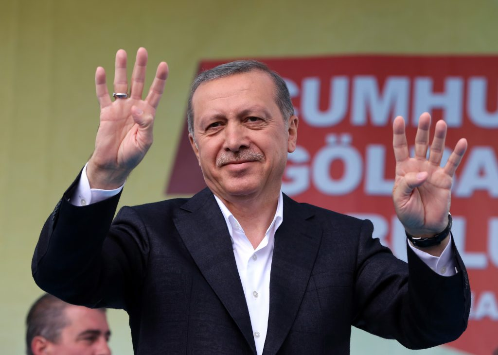 Turkey's President Recep Tayyip Erdogan salutes supporters as he addresses an election rally ahead of the upcoming June 7, 2015 general election in Golbasi, Ankara, Turkey, Friday, June 5, 2015. The overarching drama of the election has been whether Erdogan's Justice and Development Party, or AKP, will win a strong enough majority to change the constitution and put Erdogan at the unquestioned pinnacle of Turkish politics in a new presidential system.(AP Photo/Burhan Ozbilici)
