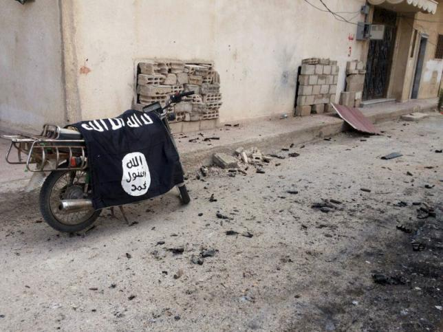 A flag belonging to the Islamic State fighters is seen on a motorbike after forces loyal to Syria's President Bashar al-Assad  recaptured the historic city of Palmyra, in Homs Governorate in this handout picture provided by SANA on March 27, 2016. REUTERS/SANA/Handout via Reuters