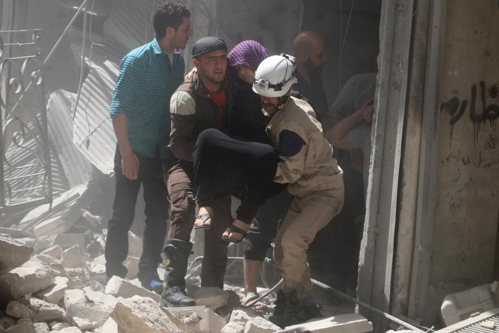 Civil defense members evacuate a woman from a damaged building after airstrikes in the rebel held area of old Aleppo, Syria. REUTERS/Abdalrhman Ismail
