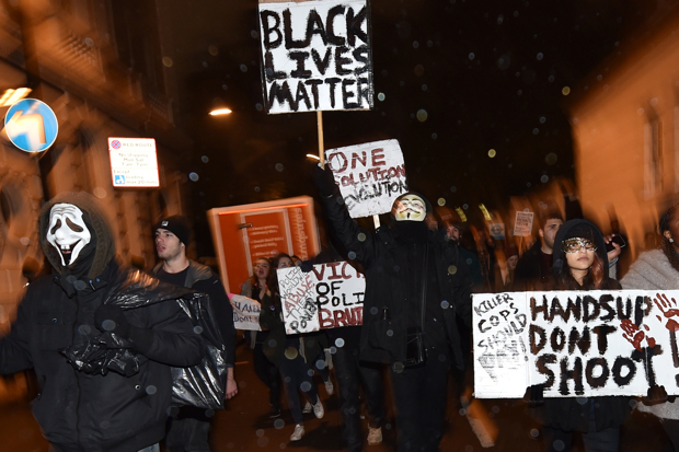 Demonstrators hold up placards as they march along a street in central London on November 26, 2014 during a protest over the US court decision not to charge the policeman who killed unarmed black teenager Michael Brown in the town of Ferguson. The policeman whose killing of unarmed black teenager Michael Brown sparked weeks of riots in the US town of Ferguson will not face charges, the county prosecutor said on November 25, amid mounting anger in the streets. Over a thousand people demonstrated outside the US embassy in London, holding up their hands and waving placards. The demonstration then turned into a march along Oxford Street, one of central London's main retail and shopping streets. AFP PHOTO / LEON NEAL        (Photo credit should read LEON NEAL/AFP/Getty Images)