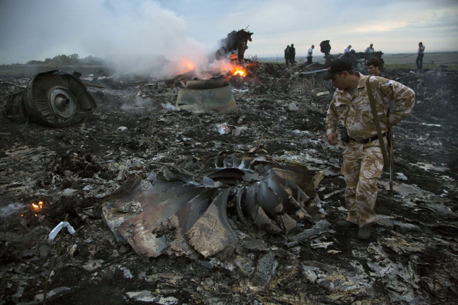 People walk amongst the debris at the crash site of a passenger plane near the village of Grabovo, Ukraine, Thursday, July 17, 2014. Ukraine said a passenger plane carrying 295 people was shot down Thursday as it flew over the country, and both the government and the pro-Russia separatists fighting in the region denied any responsibility for downing the plane. (AP Photo/Dmitry Lovetsky)/2014-07-18 07:16:13/