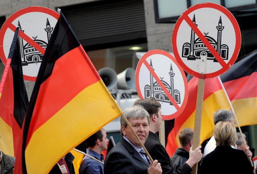 Teilnehmer einer Veranstaltung der rechtspopulistischen Partei Pro NRW tragen am Samstag (01.05.10) in Solingen Bundesflaggen und Schilder mit einer durchgestrichenen Moschee. Nach Polizeiangaben protestierten in Solingen am Samstag um die 500 Demonstranten gegen die Demonstration von 70 Anhaengern von Pro NRW.   Foto: Clemens Bilan/ddp