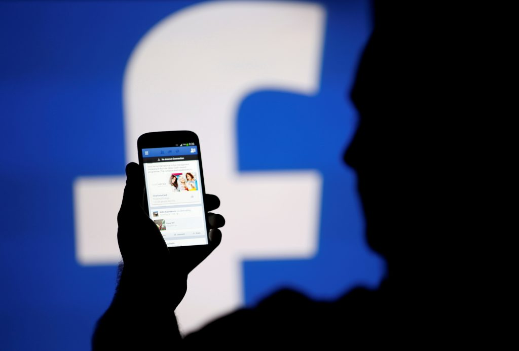 A man is silhouetted against a video screen with a Facebook logo as he poses with a Samsung S4 smartphone in this photo illustration taken in the central Bosnian town of Zenica, August 14, 2013. REUTERS/Dado Ruvic/File Photo