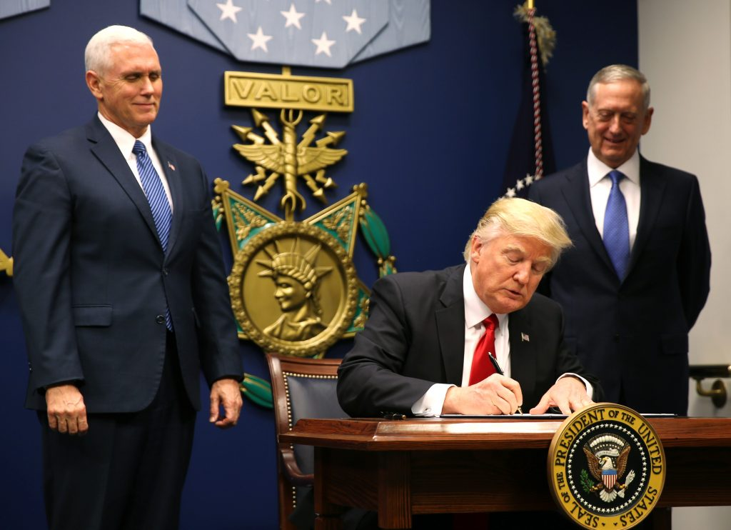 U.S. President Donald Trump (C) signs an Executive Order establising extreme vetting of people coming to the United States after attending a swearing-in ceremony for Defense Secretary James Mattis (R) with Vice President Mike Pence at the Pentagon in Washington, U.S., January 27, 2017. REUTERS/Carlos Barria