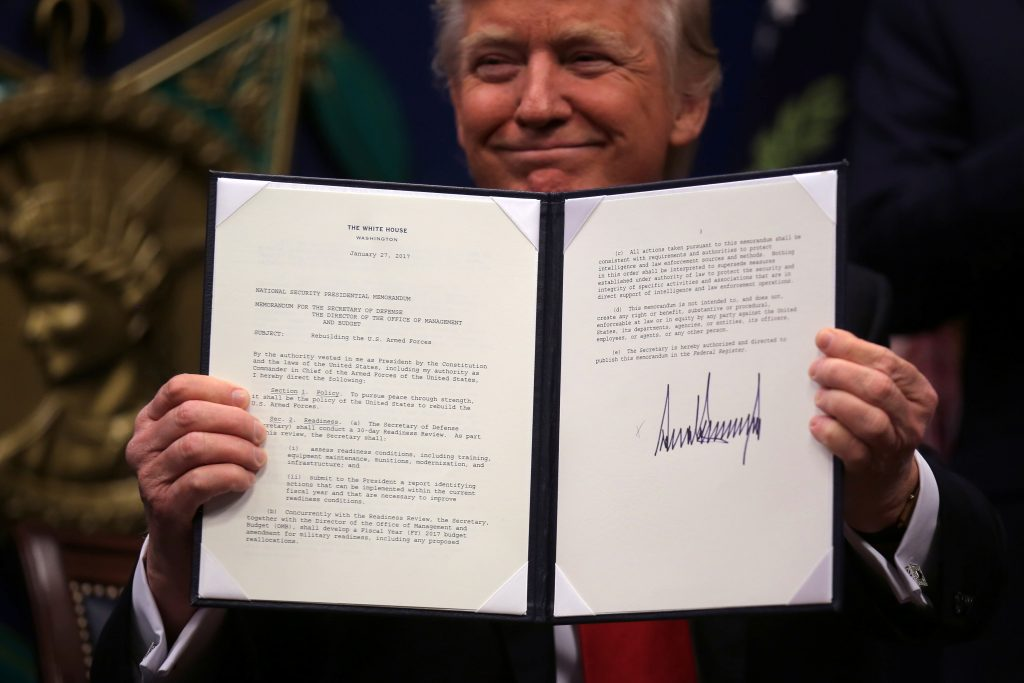 "U.S. President Donald Trump shows an executive action he said would begin the rebuilding of the U.S. military by ""developing a plan for new planes, new ships, new resources and new tools for our men and women in uniform"" after signing it, at the Pentagon in Washington, U.S., January 27, 2017. REUTERS/Carlos Barria"